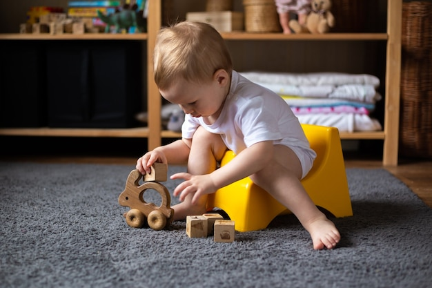 Fille mignonne de tout-petit, formation de pot, jouant avec ses jouets sur pot