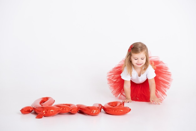 Fille mignonne de tout-petit avec l'inscription amour de ballons sur fond blanc. la saint-valentin.