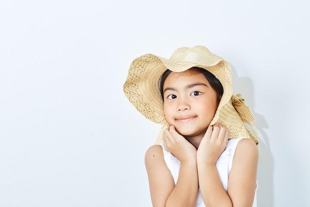 Fille mince asiatique coiffé d'un chapeau sur fond blanc.