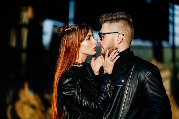 Une fille mince aux cheveux rouges vêtue de noir touche la barbe de son petit ami dans un bâtiment abandonné au coucher du soleil
