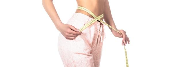 Fille mince avec centimètre. femme gros plan mesurant sa taille avec du ruban adhésif. corps de femme mince. femme avec ruban à mesurer. notion de perte de poids. une femme prend du ruban adhésif pour montrer sa taille fine.