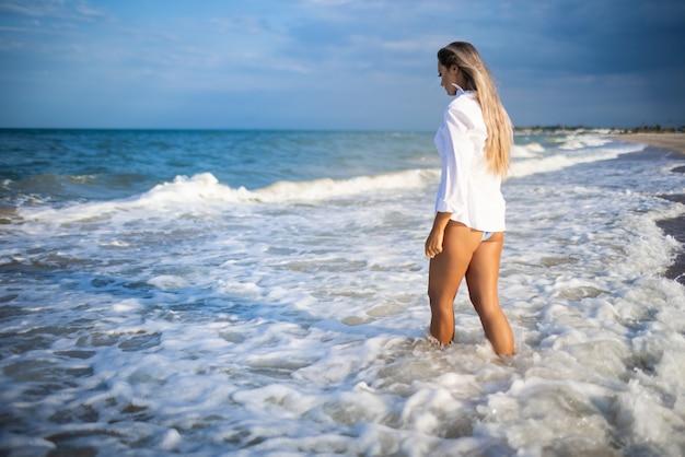 Une fille mince dans un maillot de bain bleu doux et une chemise se promène le long de la plage de sable près de la mer bleue
