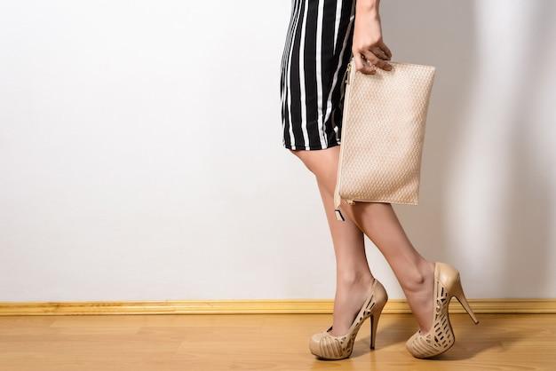 Fille mince dans une robe à rayures noires et blanches chaussures à talons hauts beige tient une pochette