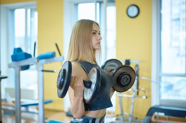 Fille mince avec des haltères dans la salle de gym.