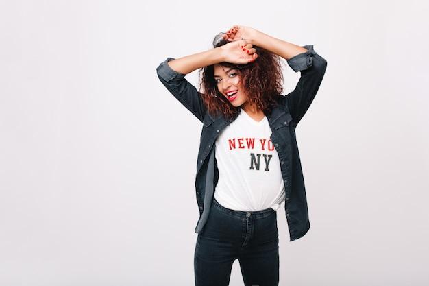 Fille mince inspirée dans un pantalon en jean dansant et riant. heureuse jeune femme noire avec manucure rouge posant avec les mains en s'amusant.