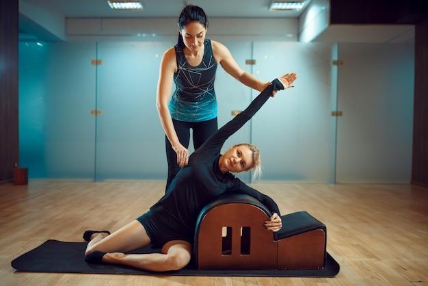 Fille mince avec instructeur, formation de pilates sur tapis dans la salle de gym. workuot de remise en forme dans un club de sport.