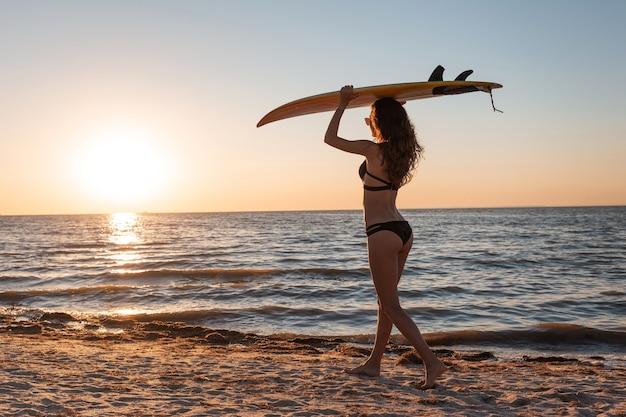Une fille mince en maillot de bain noir tient une planche de surf au-dessus de sa tête sur la plage de sable près de la mer au coucher du soleil.