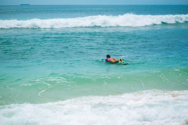 Fille mince sexy à cheval sur une planche de surf dans l'océan. mode de vie sain et actif dans la vocation estivale.