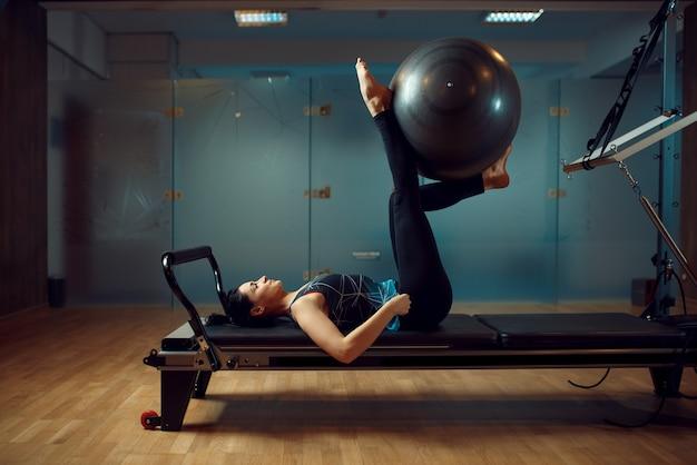 Fille mince en tenue de sport, formation de pilates avec ballon sur machine d'exercice dans la salle de gym. workuot de remise en forme dans un club de sport.