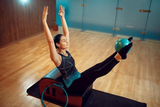 Fille mince en tenue de sport sur la formation de pilates avec ballon sur tapis dans la salle de gym. workuot de remise en forme dans un club de sport.