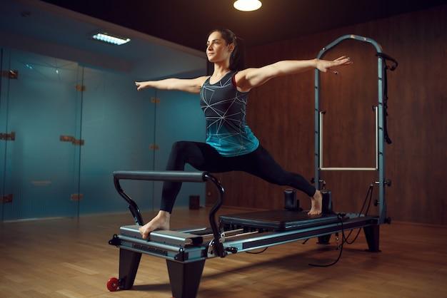 Fille mince en tenue de sport garde l'équilibre, formation de pilates sur machine d'exercice dans la salle de gym. workuot de remise en forme dans un club de sport.