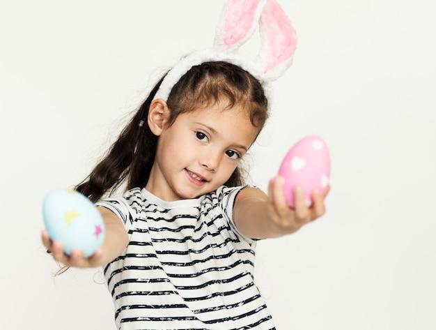 Une fille a mis une oreille de lapin rose sur la tête.