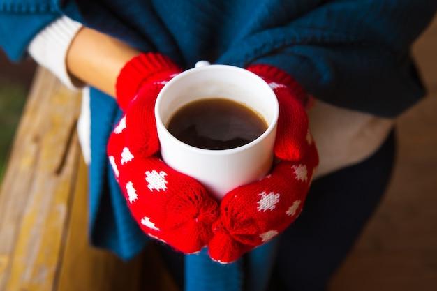 Fille en mitaines rouges tenant une tasse de café