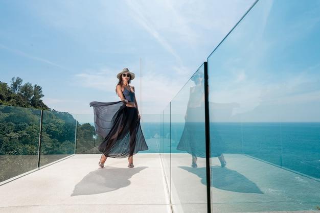 Fille à la mode avec des accessoires élégants dans un chapeau, une jupe longue posant sur un balcon transparent donnant sur la mer et la forêt tropicale