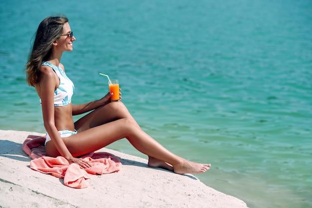 Fille à la mode, assis sur le plaid et boire un cocktail sur la plage. heureuse femme bronzée dans des lunettes de soleil élégantes et un bikini de mode profitant de vacances paradisiaques sur la plage.