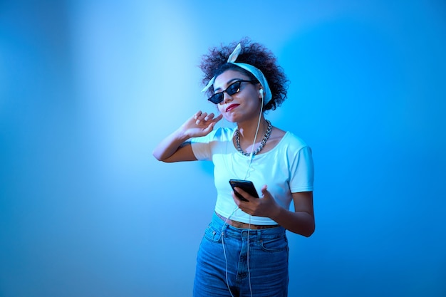 Une fille à la mode avec des boucles afro écoute et apprécie la musique avec des écouteurs à la lumière du néon bleu, des danses de modèle de style hip hop et se détendre