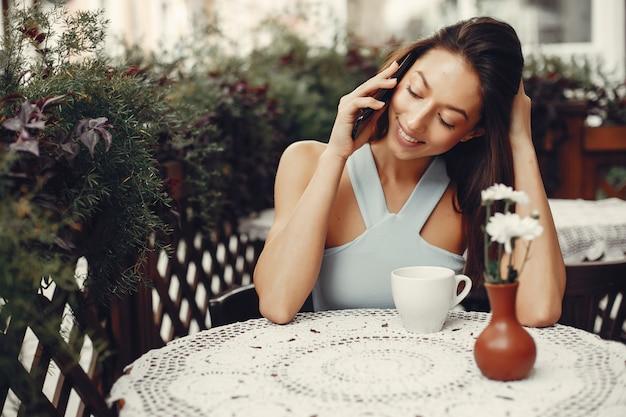 Fille de mode buvant un café dans un café