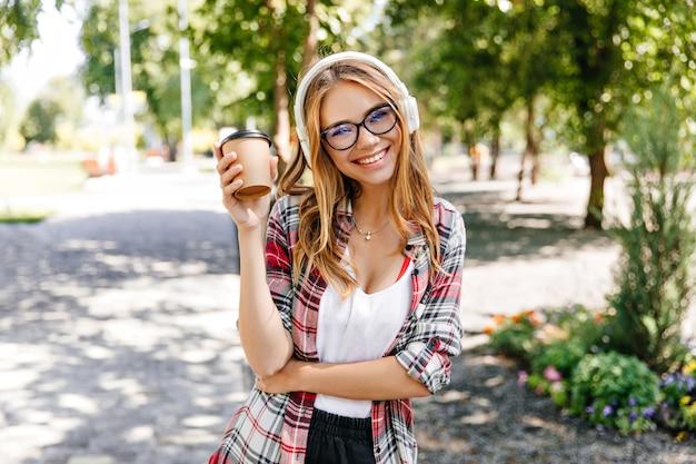 Fille à la mode avec une coiffure droite posant avec une tasse de café. portrait de femme charmante en riant, profitant de la vue sur la nature et écoutant de la musique.