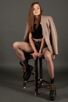 Fille à la mode en cuir posant dans une chaise
