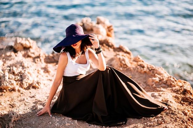 Fille à la mode dans un grand chapeau posant sur un rocher sur la plage