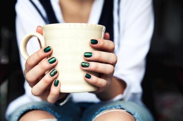 Fille à la mode élégante avec une tasse de café et une manucure verte en jeans.