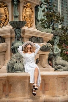 Fille de mode féminine en robe blanche et chapeau voyageant dans la vieille ville d'europe