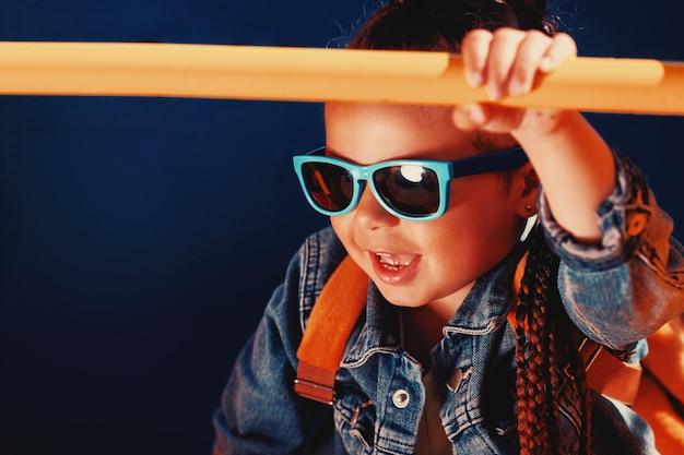 Une fille à la mode en lunettes de soleil s'accroche à la barre transversale. photo tonique. photo de haute qualité