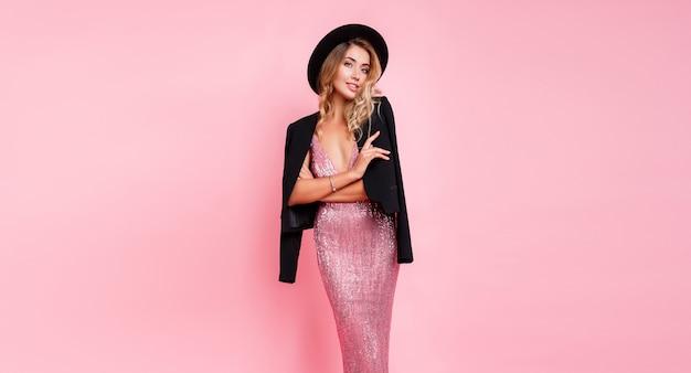 Fille à la mode en robe de soirée rose avec des paillettes posant sur un mur rose. tenue élégante. look mode haute.