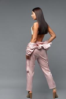 Fille de mode en salopette rose sur fond gris. espace de copie.