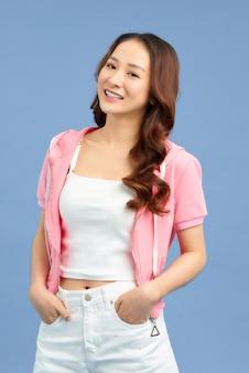 Fille à la mode en t-shirt blanc d'été décontracté et jean blanc court avec veste rose isolée sur fond bleu.