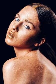 Fille de modèle d'art de mode de beauté avec la peau d'or. bouchent portrait de fille aux yeux bleus sur fond noir