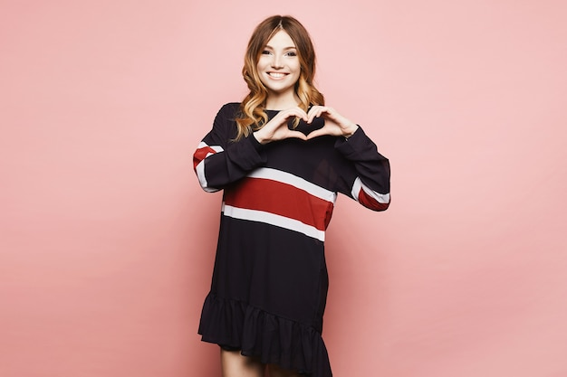 Fille modèle belle et à la mode en robe élégante s'amuser, montrer un cœur par ses bras et posant sur fond rose