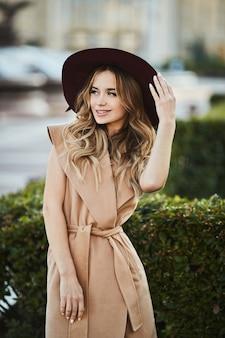 Fille modèle blonde belle et sensuelle à la mode en manteau sans manches ajustant son chapeau élégant, souriant et posant à l'extérieur dans la rue de la ville