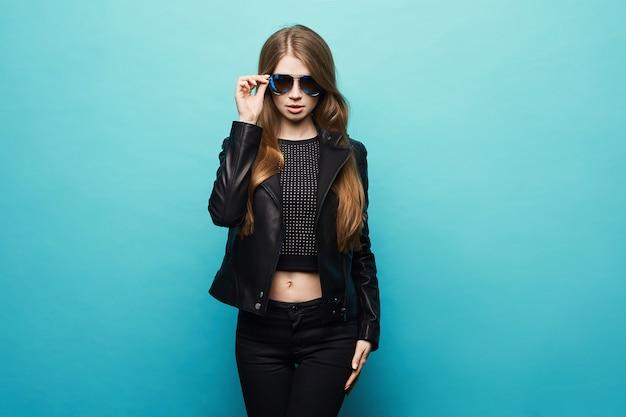 Fille modèle blonde à la mode avec un corps parfait dans la veste en cuir noire et des lunettes de soleil élégantes posant sur le bleu. copiez l'espace pour votre texte.