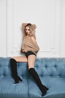 Fille modèle blonde sexy et belle avec un maquillage lumineux et un corps séduisant parfait en lingerie noire élégante et en sweat-shirt est assis sur un canapé et posant à l'intérieur
