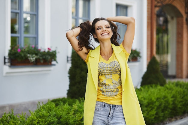 Fille modèle brune avec un maquillage lumineux et avec un sourire charmant dans un manteau sans manches jaune élégant, amusez-vous et posant à la rue de la ville