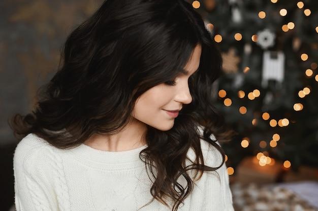 Fille modèle brune posant dans un intérieur avec des lumières de noël festives sur le fond.