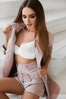 Fille modèle avec un corps parfait et des lèvres charnues portant une veste déboutonnée et un soutien-gorge blanc posant à l'intérieur.