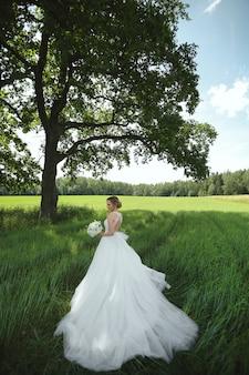 Fille modèle dans une luxueuse robe de mariée avec bouquet de fleurs de mariée posant dans le champ vert près de l'arbre seul le jour d'été