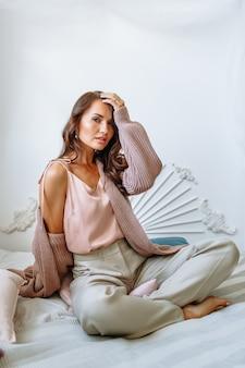 Fille modèle dans une veste tricotée sur le lit.