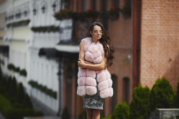 Fille modèle élégant en gilet de fourrure à la mode marchant dans la rue de la ville. concept de mode de rue.