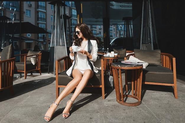 Une fille modèle avec de longues jambes sexy dans un costume élégant boit du café à l'extérieur à une table de café un jour d'été
