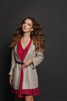 Une fille modèle avec un maquillage et une coiffure parfaits portant une robe rose et un trench-coat à la mode posant sur fond noir