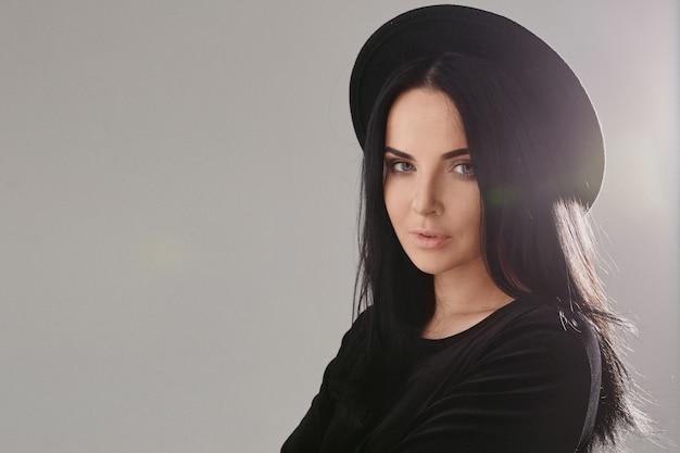 Fille modèle avec un maquillage parfait et des cheveux noirs portant un chapeau noir isolé sur fond gris avec espace de copie