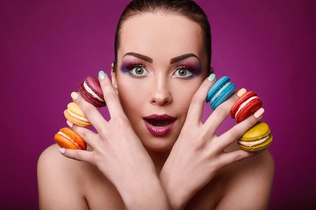 Fille de modèle de mode beauté glamour avec maquillage coloré et macarons.