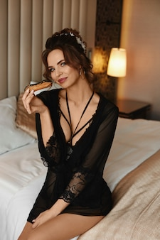 Fille modèle sexy en lingerie noire et avec une coiffure élégante tenant un gâteau au chocolat à la main et assis sur le lit. beauté, concept de mode