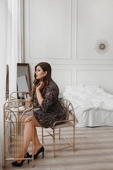 Fille modèle sexy de taille plus assis à la coiffeuse et regardant le miroir. jeune femme dodue avec un maquillage lumineux en robe, préparant la célébration. grosse femme dans une tenue à la mode. mode xxl.