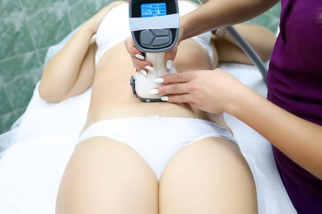 Une fille modèle en sous-vêtements blancs se trouve devant le maître sur la procédure d'élimination de la cellulite sous vide par massage