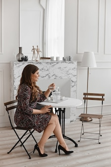 Fille de modèle de taille plus sexy en robe tendance, assis à la table et posant à l'intérieur. jeune grosse femme avec un maquillage lumineux et avec une coiffure élégante dans une tenue à la mode. mode et beauté xxl.