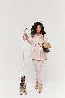 Fille modèle avec tasse de café et boîte de nourriture dans ses mains posant avec mignon york terrier sur fond blanc, isolé. annoncez le concept
